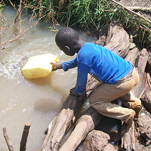 A boy gathering dirty water.  Lack of access to clean water is a crisis.